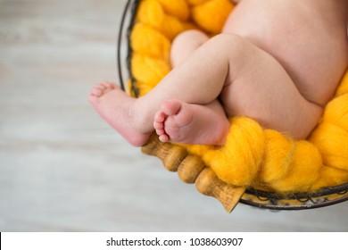 newborn legs on yellow wool blanket inside a basket