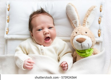 Newborn little baby wearing a warm knitted jacket playing with toy bunny relaxing on white knit blanket in sunny nursery. Kids winter clothing and bedding. Hand made toys and textile for children