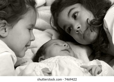A newborn little girl and her sisters. Family, love, caring.