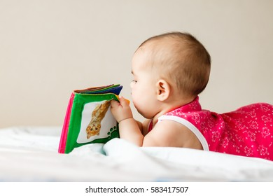 newborn on the bed with the children's book