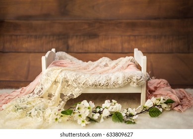 Newborn photo shoot set up with prop bed and wood backdrop