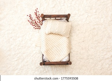 Newborn photography background - rustic wooden bed  with white chunky blanket, knitted pillow on white fluffy backdrop with red berries