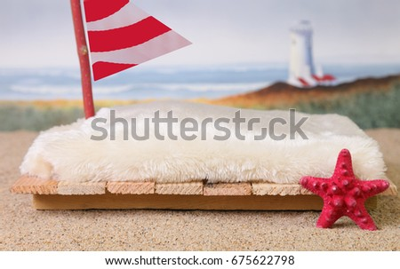 A newborn photography prop of a raft at the beach with sand, a red starfish, a red and white sail and a lighthouse and ocean waves in the blurred background.