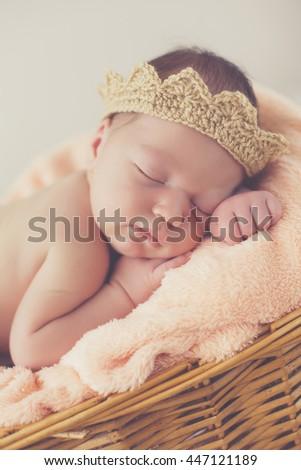 A newborn premature baby boy sleeping in a basket wearing a hat. Cute happy newborn  baby in a blue knit cap sleeping in a basket. little newborn baby boy or ... 02acd77ccdca