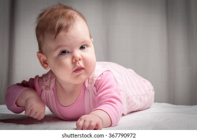 Newborn pretty baby girl in pink baby clothes