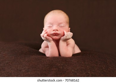 Newborn  propped up with head on hands