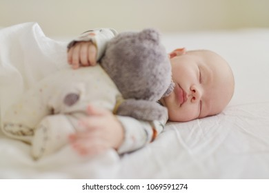 newborn is sleeping with bear on the bed