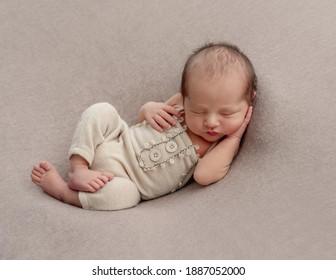 Neugeborener schläft mit Hand unter Kopf