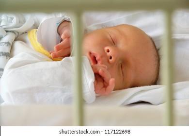 Newborn sleeping in hospital crib