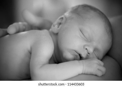 Newborn sleeping infant on mother black and white