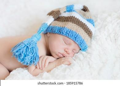 newborn sleeping at white wearing funny cap