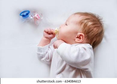 A newborn is sucking a pacifier. - Shutterstock ID 634084613