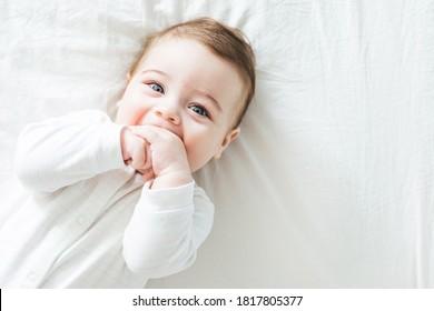 Neugeborener Junge, der auf dem Bett lacht und die Kamera mit Draufsicht anschaut