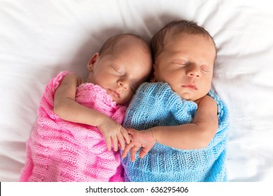 Newborn twins sleeping on bed together