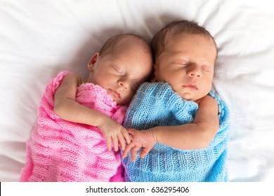 Newborn twins sleeping on bed together