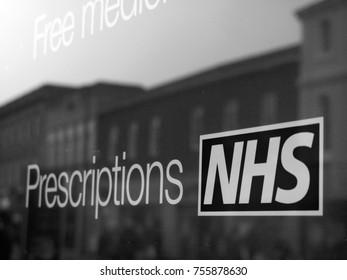 Newbury, Berkshire, England - November 3, 2017: Monochrome NHS, National Health Service prescriptions sign in pharmacy shop window
