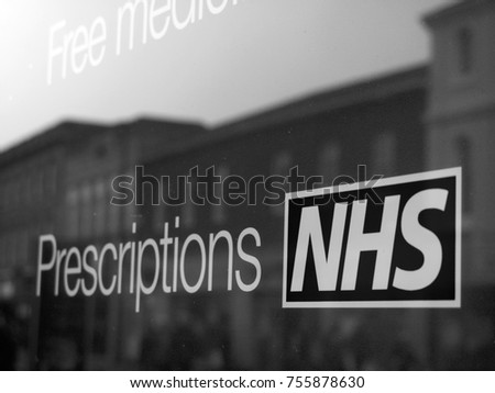 Newbury, Berkshire, England - November 3, 2017: Monochrome NHS, National Health Service prescriptions sign in pharmacy shop window