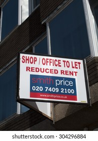 Newbury, Market Place, Berkshire, England - August 07, 2015: Shop office to let with reduced rent advertising sign over vacant premises