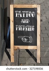 Newbury, Market Place, Berkshire, England - October 10, 2015: Tattoo and piercing sign outside premises