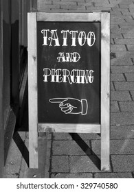 Newbury, Northbrook Street, Berkshire, England - October 10, 2015: Sign outside on pavement for tattoo and piercing shop