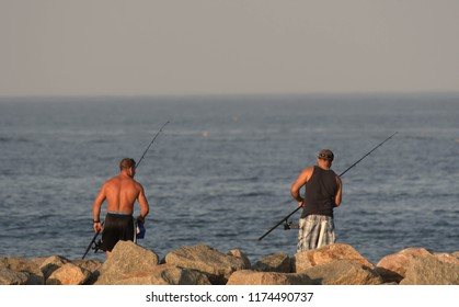 Newburyport, Mass./USA - Sept. 3, 2018: Two men fish on a jetty at sunset on Labor Day.