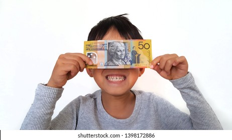Newcastle, Australia - May 2019: Australia fifty dollar bank note (50 AUD) holding by smiling boy with both hands in isolated white background.