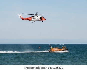 Newcastle, Co. Down, Northern Ireland - June 22, 2019: The annual Festival of Flight attracts over 100,000 visitors to the seaside town. Irish Coast Guard helicopter and RNLI lifeboat on exercise