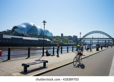 NEWCASTLE, ENGLAND - MAY 9, 2016: Newcastle Quayside.  People are making their way along the quayside.  Tyne Bridge, River Tyne and Sage Gateshead are in shot.  A cyclist is riding along the bus lane.