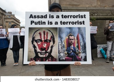 Newcastle / Great Britain - June 15, 2019 : Young Anti war protester holding a banner placard protesting against the war in Syria.  Anti Assad, Anti Putin.  Peaceful protest.