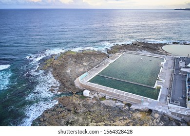 Newcastle ocean baths aerial drone view just after sunrise on overcast day
