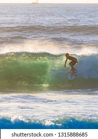 Newcastle Ocean Baths, Newcastle, NSW / Australia - February 17 2019: Young surfer surfing at sunrise