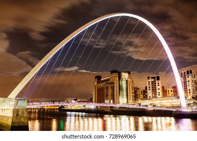 Newcastle, UK 05/10/2017 The Gateshead Millennium Bridge at night, with Baltic Centre for Contemporary Arts behind, viewed from Newcastle Quayside.