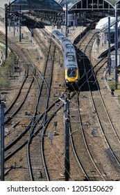Newcastle upon Tyne, England - April 10 2016; vertical format image of train departing northwards from Newcastle Central Station, tracks and overhead electric cables in foreground