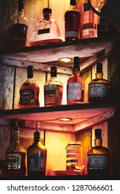 NEWCASTLE UPON TYNE, ENGLAND, UK - JUNE 01, 2016: Bottles of Rum, Whisky and Brandy on a rustic shelf in a bar.