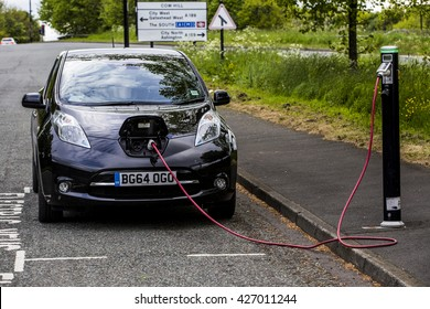NEWCASTLE UPON TYNE, UK - 20 May 2016.  An Electric Nissan Leaf car parked on the roadside charging from a a public charging point.