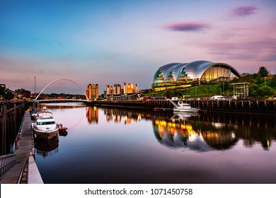 Newcastle upon Tyne, UK. Famous Millennium bridge at sunset. Illuminated landmarks with river Tyne in Newcastle, UK and colorful sky