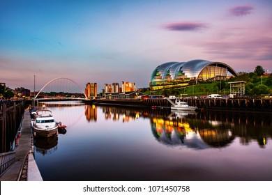 Newcastle upon Tyne, UK. Famous Millennium bridge at sunset. Illuminated landmarks with river Tyne in Newcastle, UK and colorful sky