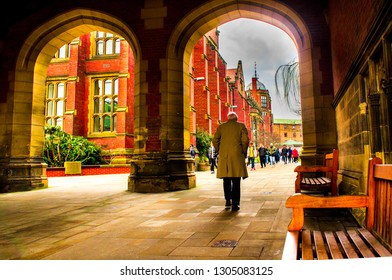 Newcastle upon tyne, Tyne and wear / England - February 5 2019 - An old man in an overcoat walking through the Arches at Newcastle University.
