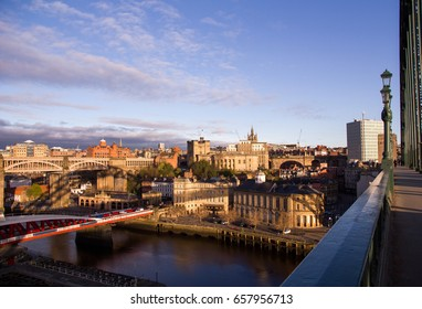 Newcastle Upon Tyne's Quayside and Grainger Town areas coloured golden at sunrise, with shadow of the iconic Tyne Bridge cast across the buildings