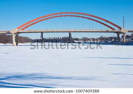 newer highway 61 tied-arch bridge and older vertical lift rail bridge spanning frozen mississippi river in hastings minnesota