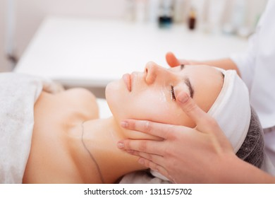 Newest procedures. Pleasant young woman enjoying the cosmetology treatment while lying with cream on her face