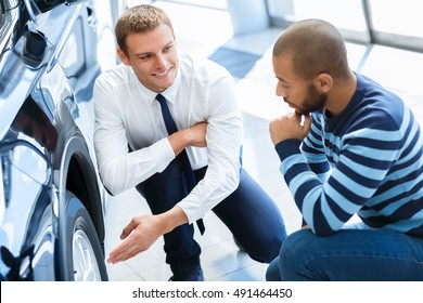 Newest tires technologies. Shot of a professional salesman talking to his client while showing him wheels of a car the customer is buying
