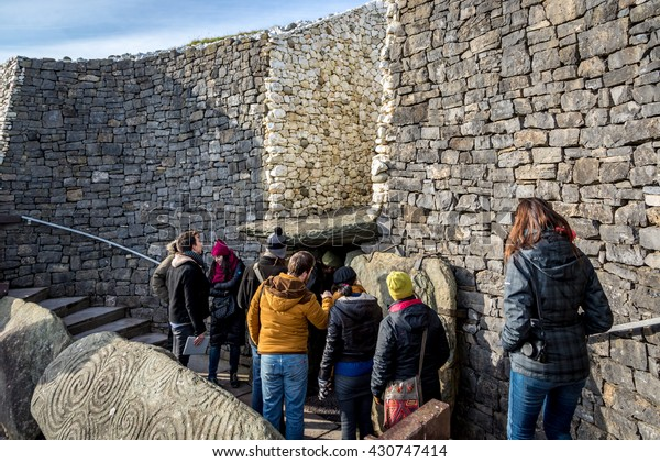 Newgrange, Ireland - February 15th 2015 - Tourists entering in the Newgrange Stone Age Passage Tomb in a blue sky day, winter time, Newgrange, Ireland