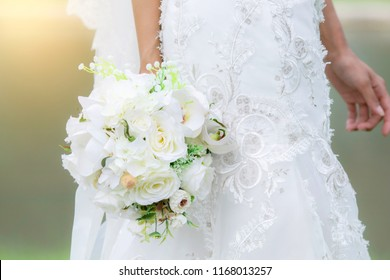 Newly beautiful bride no face with white wedding dress hold the flowers bouquet walk around the garden with copy space / bride with bouquet concept
