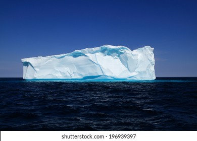 Newly born Iceberg. Piece 500 m long 10000 years old ice broken from glaciers or ice shelves in Western Greenland, shaped as ice cube on move to Iceberg Alley around Labrador and Newfoundland coasts