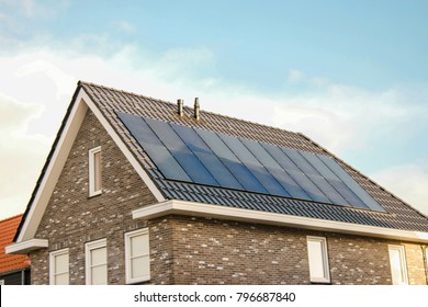 Newly build house in the Netherlands with solar panels attached on the roof against a sunny sky Close up of new building  black solar panels.Zonnepanelen Translation: Solar  panel, Sun energy