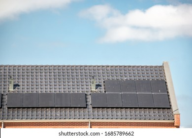 Newly build houses in the Netherlands with solar panels attached on the roof against a sunny sky Close up of new building black solar panels