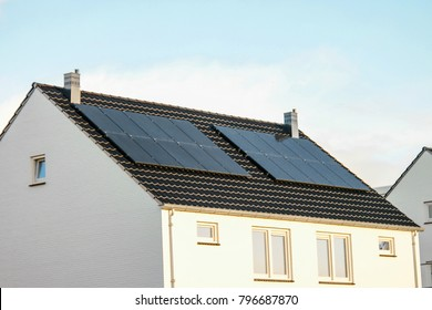 Newly build houses in the Netherlands with solar panels attached on the roof against a sunny sky Close up of new building  black solar panels.Zonnepanelen Translation: Solar  panel, Sun energy
