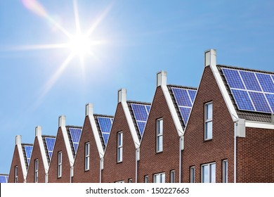 Newly build houses with solar panels attached on the roof against a sunny sky
