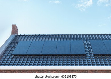 Newly build houses with solar panels attached on the roof against a sunny sky Close up of new building with black solar panels.( Zonnepanelen )Translation:  Solar  panel, Zonne energie, Sun Energy